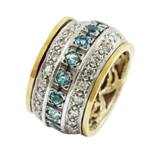 Silver and 9k gold revolving ring set with blue topaz and Cubic Zircona gems. Revolving rings are also called Tibetan worry rings. A revolving, or spinner ring consists of an inner band and outer bands, where the outer bands spin freely around the inner b