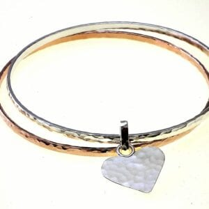 Adorable sterling silver and 14k rolled gold bangles with a heart charm